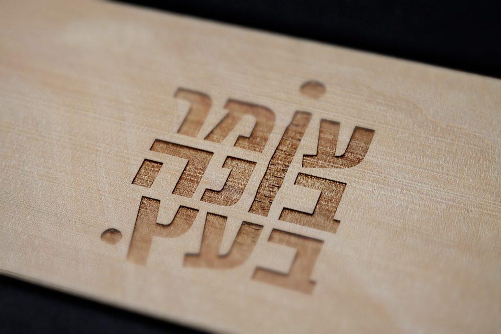 """לוגו """"עומר בונה בעץ"""" מוטבע על עץ"""